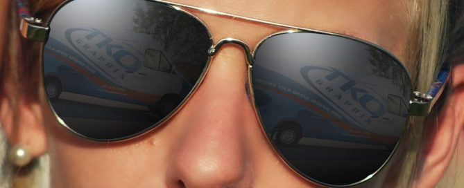 Person wearing aviator sunglasses with TKO Graphix van wrap reflection in the lenses