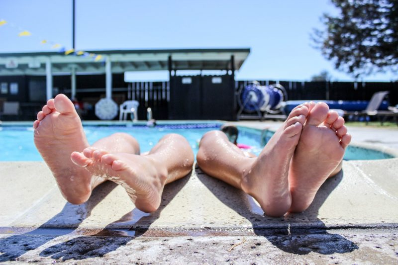 4 feet resting on the edge of a swimming pool in summer