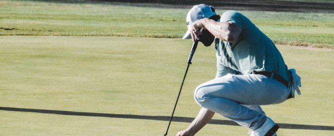 Mna picking his ball out of the pin on the green of a golf course
