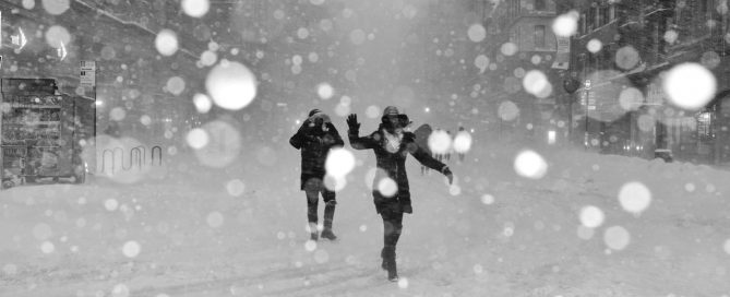 two people on a city street in a snow storm