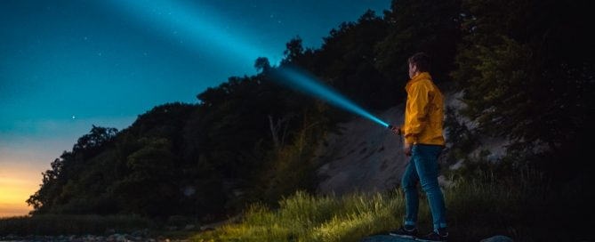 man in woods shining a flashlight at the sky